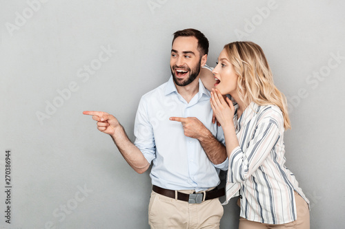 Fotografie, Obraz  Photo of excited couple in casual clothing looking aside while pointing fingers