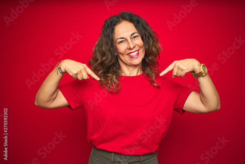 Photo  Middle age senior woman with curly hair over red isolated background looking confident with smile on face, pointing oneself with fingers proud and happy