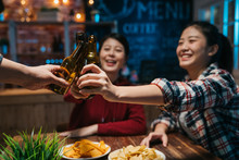 Group Of Happy Friends Drinking And Toasting Beer At Brewery Bar Restaurant In Late Night. Friendship Concept With Young People Having Fun Together At Cool Vintage Pub. Focus On Hands Bottle Alcohol