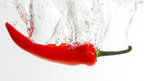 red chili pepper falling in water. healthy fresh vegetables and food.