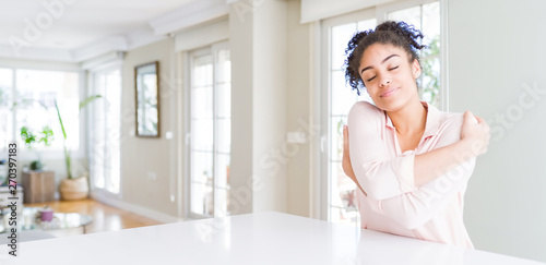 Wide angle of beautiful african american woman with afro hair Hugging oneself happy and positive, smiling confident Wallpaper Mural