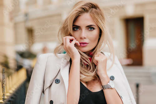 Close-up portrait of adorable blonde girl with pink lipstick playfully posing on blur street background Tablou Canvas