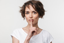 Portrait Of Kind Woman With Short Brown Hair In Basic T-shirt Holding Index Finger On Lips