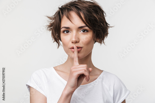 Fototapeta  Portrait of kind woman with short brown hair in basic t-shirt holding index fing