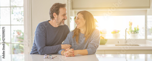 Obraz Romantic middle age couple sitting together at home - fototapety do salonu