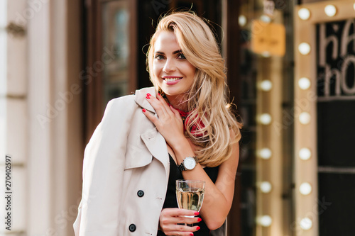 Fotografie, Obraz  Excited blonde woman in trendy silver wristwatch posing with pleasure in her birthday, holding wineglass