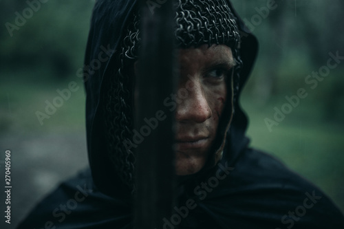 Photo Portrait of young man in the image of a medieval knight in chain armor and with a sword