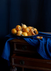 Still life with fresh medlar on the metallic plate