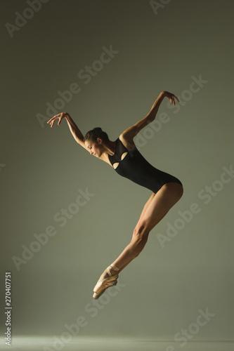 Obraz na plátně Graceful ballet dancer or classic ballerina dancing isolated on grey studio background