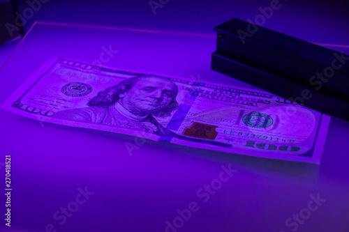 Checking the hundred dollar bill for fraud in UV light