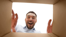 Mail Delivery And Surprise Concept - Smiling Man Taking Something Out Of Parcel Box, From Below