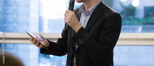 Fototapeta Speaker holding microphone in conference. Corporate executive giving speech during business training seminar. Expert presenter on stage during lecture. CEO presenting investor pitch. obraz