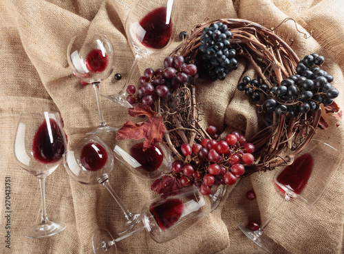 Photo  Red wine and grapes on a table covered with burlap.