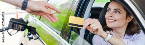Fotografie, Obraz  panoramic shot of cheerful woman sitting in car and giving credit card to worker