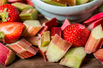 Close up of Pieces of Raw and Freshly Cut Rhubarb and Strawberries on Dark Rustic Background