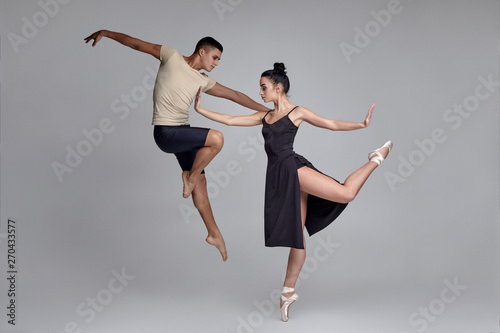 Valokuva Two athletic modern ballet dancers are posing against a gray studio background