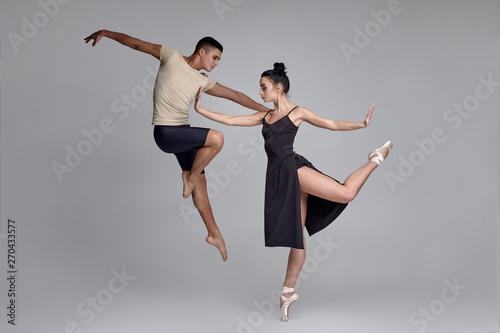Obraz na plátne Two athletic modern ballet dancers are posing against a gray studio background