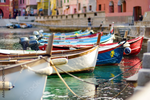 Poster Mediterranean Europe Colourful fishing boats in small marina of Vernazza, one of the five centuries-old villages of Cinque Terre, located on rugged northwest coast of Italian Riviera.