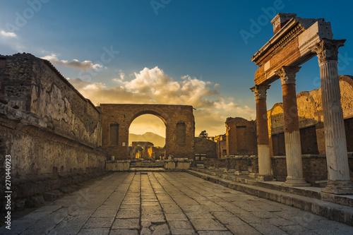 Stampa su Tela Ruins of ancient city of Pompeii, ancient roman city against Vesuvius volcano at sunset, Italy