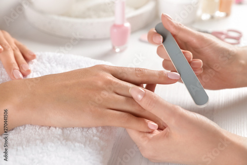 Canvas Print Manicurist filing client's nails at table, closeup. Spa treatment