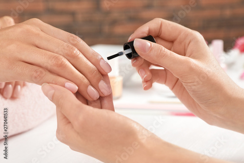 Poster Manicure Manicurist applying polish on client's nails at table, closeup. Spa treatment
