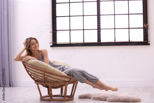 Deurstickers Ontspanning Young woman relaxing near window with blinds at home. Space for text