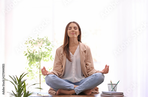 Carta da parati  Young businesswoman meditating at workplace. Zen concept
