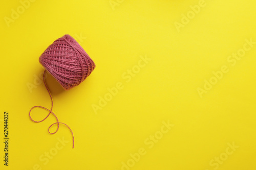 Fotografiet  Clew of knitting threads on color background, top view with space for text