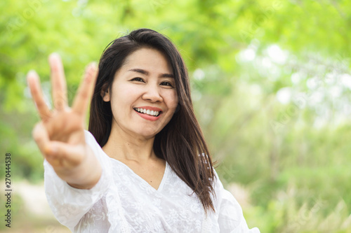 Happy Asian woman showing finger age 30 years old and smiling to camera in a par Canvas Print