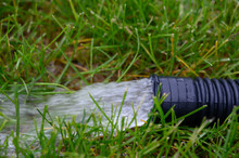 Residential Sump Pump Discharging Water From The End Of A Flexible Black Hose