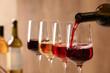 Leinwandbild Motiv Pouring wine from bottle into glass on blurred background, closeup