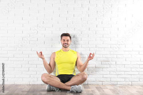 Handsome young man sitting on floor and practicing zen yoga near brick wall