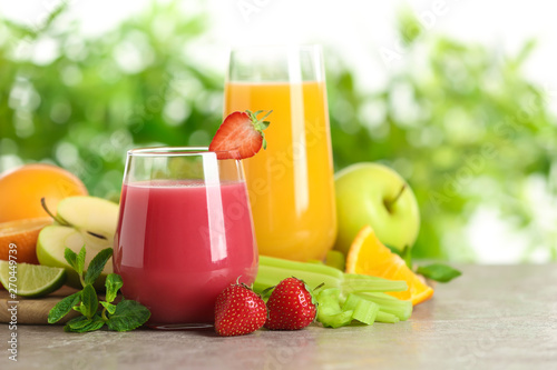 Tuinposter Keuken Glasses with different juices and fresh fruits on table against blurred background. Space for text