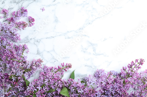Foto op Aluminium Lilac Blossoming lilac flowers on marble table, flat lay. Space for text