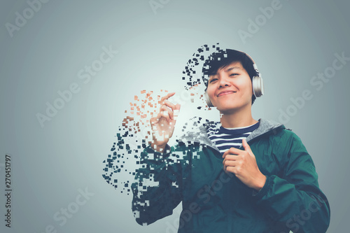 Asian man in green sweater wearing headset listen to music of dissolving into pixels on gray background Future technology Concept - 270451797