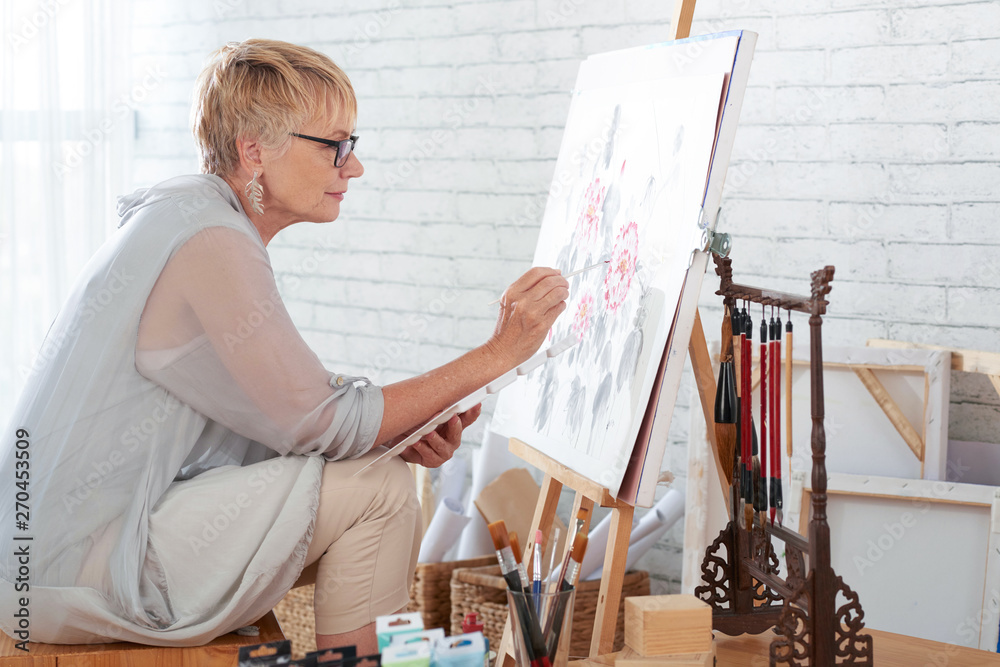 Fototapety, obrazy: Mature woman sitting in art studio in front of easel and painting a picture with paints