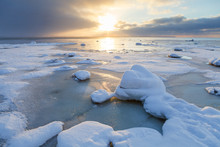 Sunset With Snowy Boulders And Beach Landscape. Baltic Sea, Winter Time.