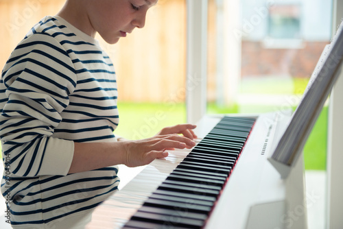 Teenager boy has training course with e-piano at home - 270459114
