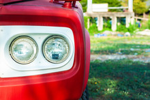 Close Up Classic Red Truck Double Headlight With White Frame And  Green Yard,