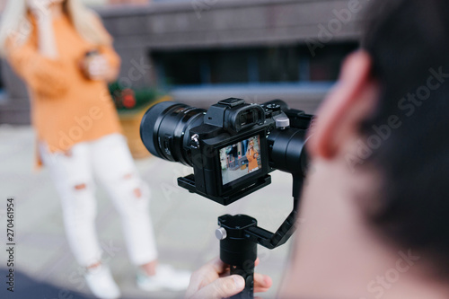 Fototapeta Portrait of girl in ripped pants and sport shoes with photographer on foreground. Brunette man holding professional camera and making photo of stylish european female model. obraz na płótnie