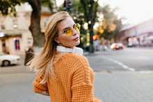 Attractive Young Woman In Knitted Orange Sweater Looking Over Shoulder With Gently Smile. Beautiful Blonde Girl In Round Glasses And Big Earphones Posing Outdoor On Blur Background.