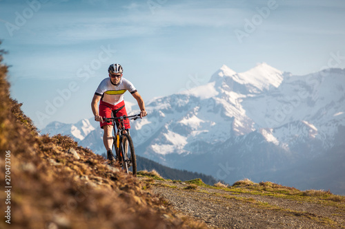 Photo  Male mountainbiker on a trail in the mountains