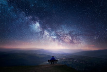 A Man Sitting On A Bench Staring At A Starry Sky With A Milky Way And A Mountain Landscape
