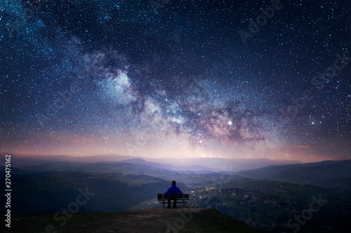 Leinwand Poster A man sitting on a bench staring at a starry sky with a Milky Way and a mountain