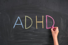 Child Writing Abbreviation ADHD On A Blackboard