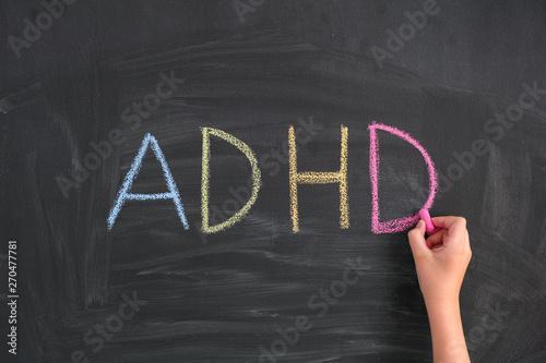 Photo Child writing Abbreviation ADHD on a blackboard