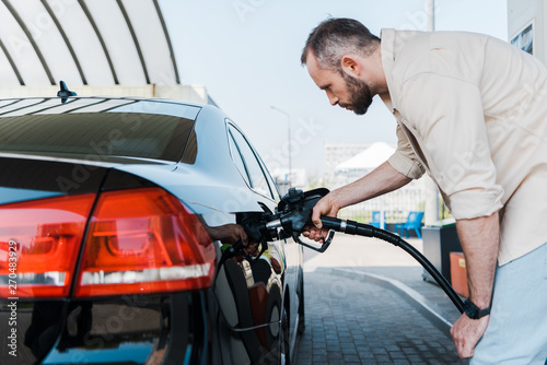 Photo  bearded man holding fuel pump and refueling black car at gas station