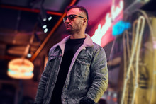 A Bearded Stylish Male Wearing A Denim Jacket And Sunglasses Looking Away While Standing In The Night On The Street. Illuminated Signboards, Neon, Lights.