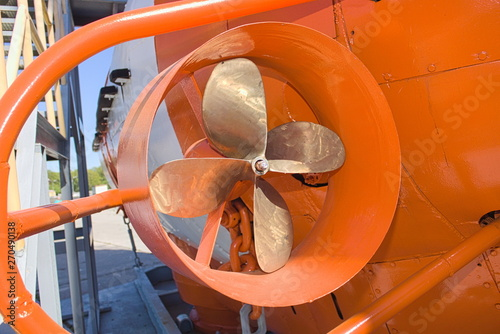 Side propeller and part of the board of the orange-white bathyscaphe on the warship desck close up.