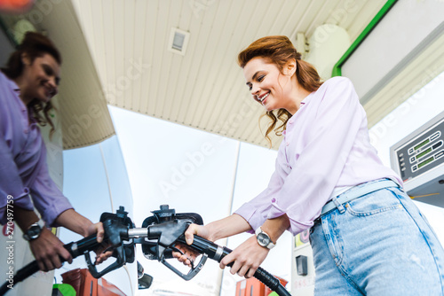 low angle view of happy woman holding fuel pump while refueling car with benzine Fototapete